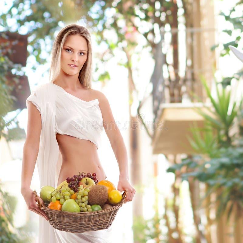 Een jonge blonde vrouw in vruchten van een de witte kledingsholding stock afbeeldingen