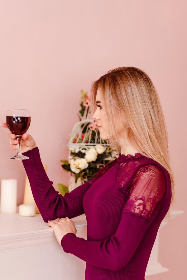Een jonge blondevrouw die een glas rode wijn binnen houden stock afbeeldingen