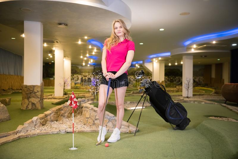 Een jonge blondevrouw in kleine zwarte borrels die zich in golfclub dichtbij de stokzak bevinden stock foto's