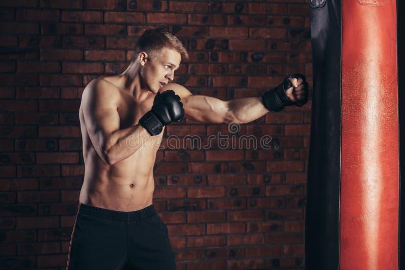 Een jonge bokser in zwarte handschoenen met een naakt torso werkt stakingen op ponsenzak uit stock afbeelding