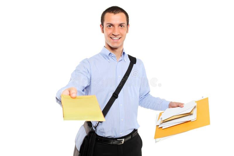 Een jonge brievenbesteller die post levert stock afbeeldingen