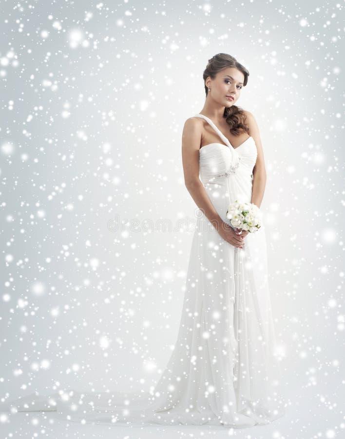 Een jonge bruid in een witte kleding op sneeuwbac stock afbeeldingen