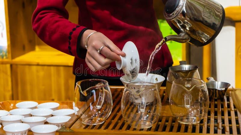 Een jonge Chinese vrouw maakt Chinese thee en giet warm water in een grote Chinees - gestileerde witte theekop stock fotografie