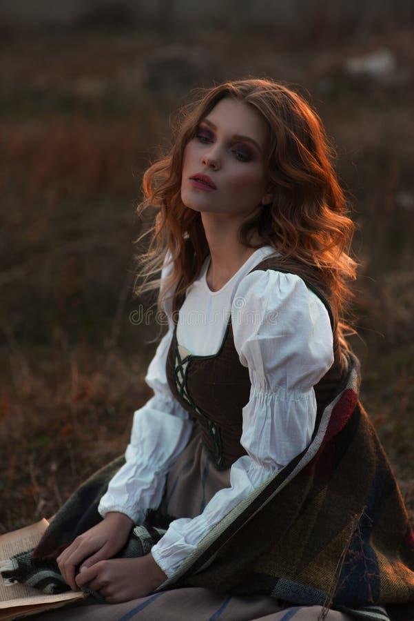 Een jonge dame in een middeleeuwse kleding met een boek stock foto