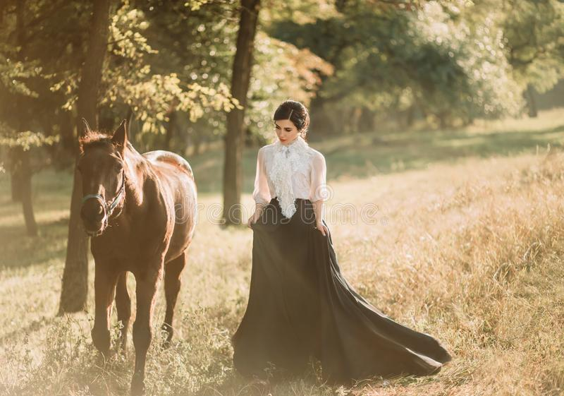 Een jonge dame in een uitstekende kleding met een lange trein, gangen met een paard door de bosopen plekken Een oud, verzameld ka royalty-vrije stock fotografie