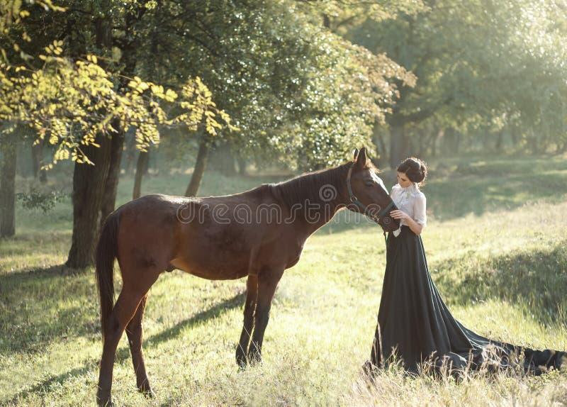 Een jonge dame in een wijnoogst kleedt zich met een lange trein, omhelst veel liefs haar paard met tederheid en affectie Oud, col stock fotografie