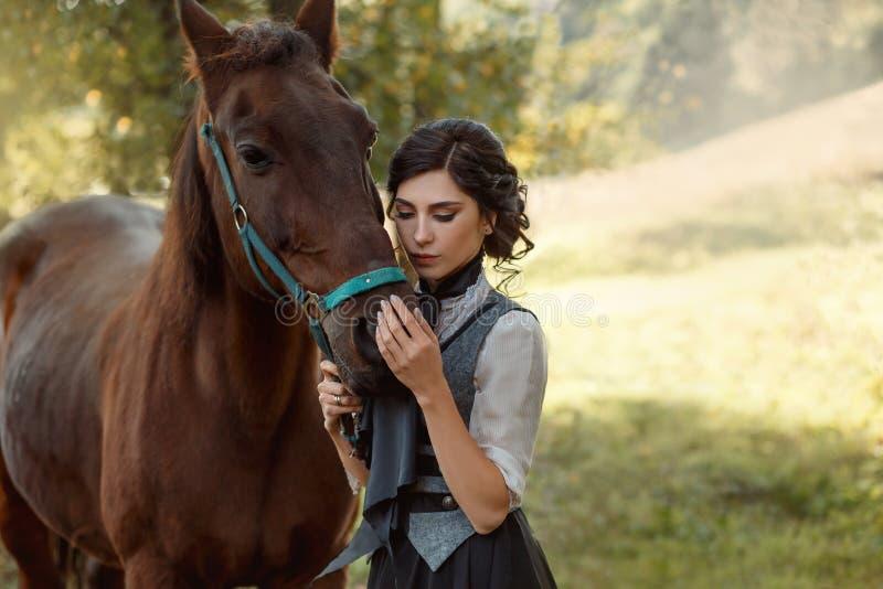 Een jonge dame in een wijnoogst kleedt zich met een lange trein, omhelst veel liefs haar paard met tederheid en affectie Oud, col stock foto's
