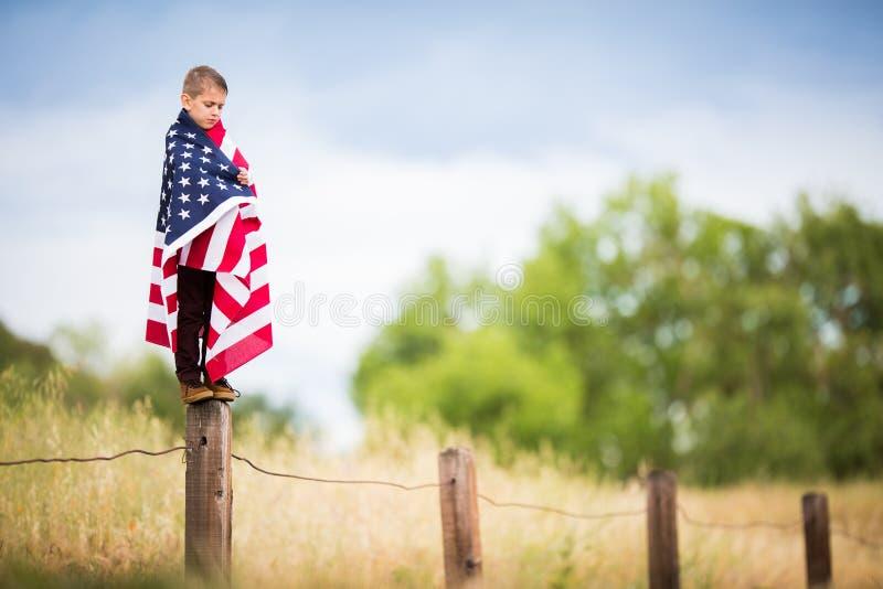 Een jonge die jongen in een grote Vlag van Amerika wordt verpakt stock foto
