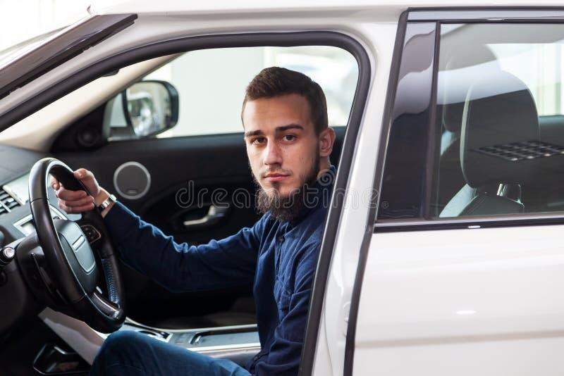 Een jonge donker-haired kerel met een baard zit achter het wiel van een witte auto en onderzoekt de camera door de open deur met  royalty-vrije stock fotografie
