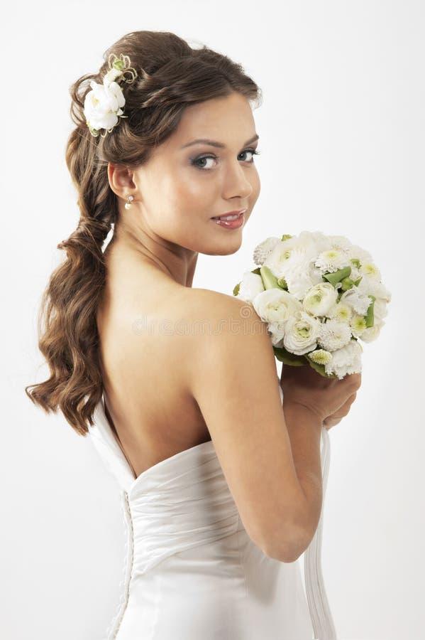 Een jonge donkerbruine bruid die een boeket van rozen houdt stock foto's