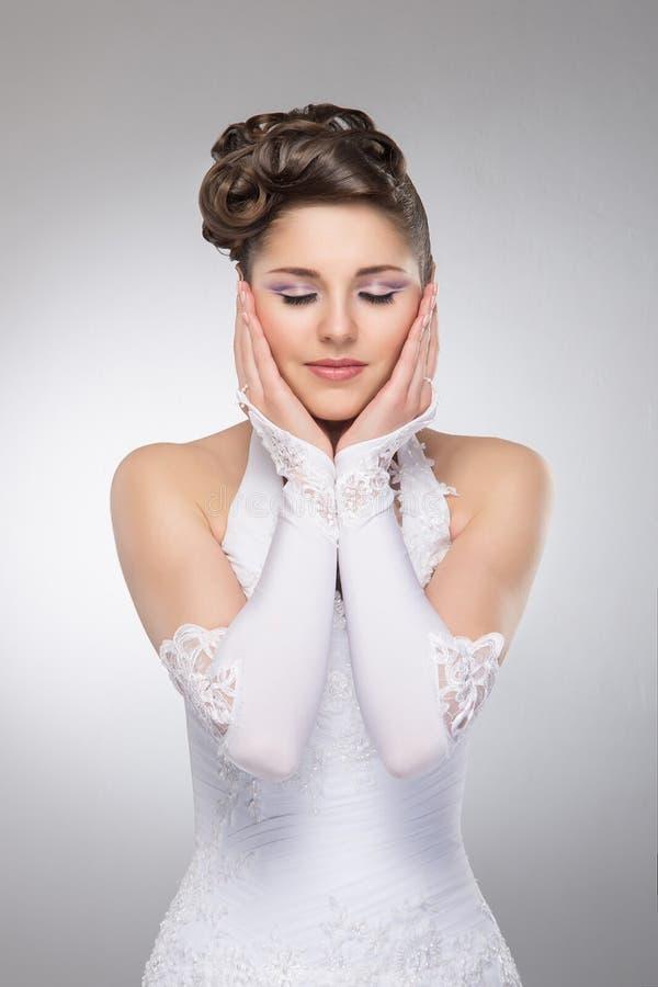 Een jonge donkerbruine bruid in een witte huwelijkskleding stock foto