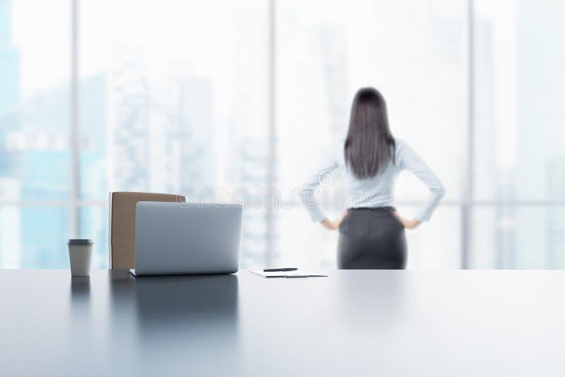 Een jonge donkerbruine dame kijkt uit het venster in het moderne panoramische bureau in Singapore Laptop, de blocnote en een koff stock foto
