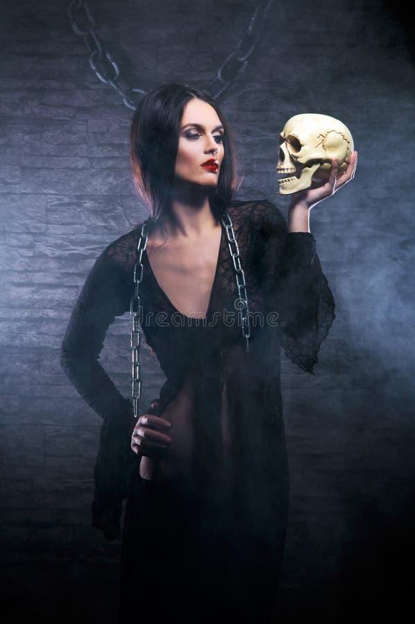 Een jonge donkerbruine heks die een menselijke schedel houdt stock afbeelding