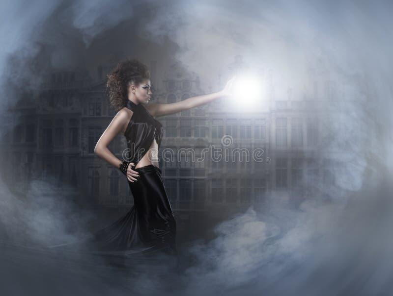 Een jonge donkerbruine tovenaar die een bliksembal giet stock afbeeldingen