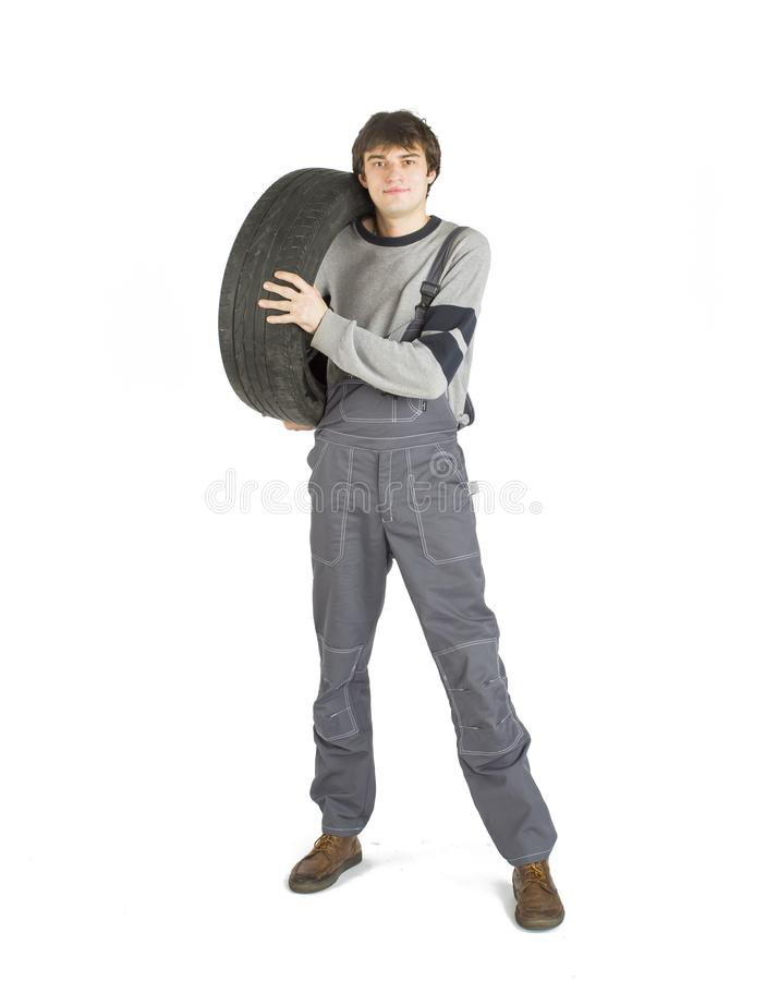 Een jonge donkerbruine voorman in het werk grijze eenvormig met zwart wiel stock afbeeldingen