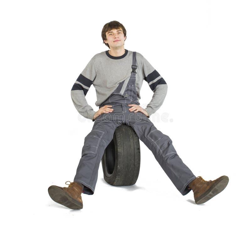 Een jonge donkerbruine voorman in het werk grijze eenvormig met zwart wiel stock afbeelding