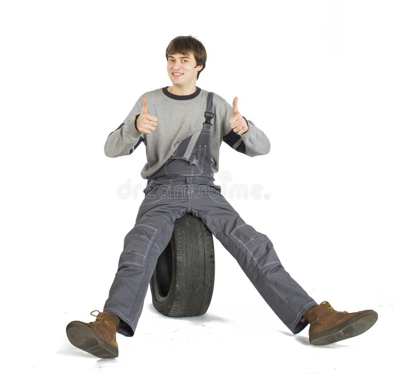Een jonge donkerbruine voorman in het werk grijze eenvormig met zwart wiel royalty-vrije stock foto