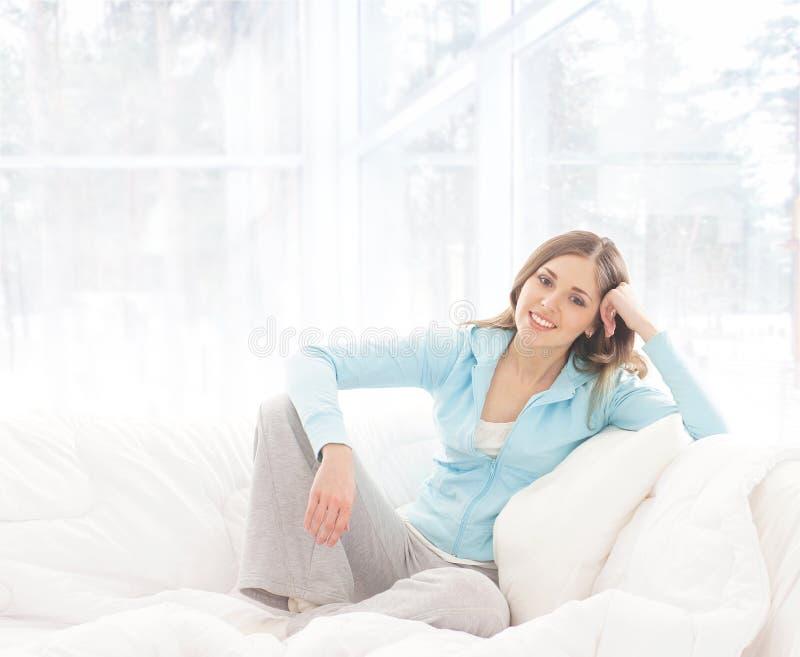 Een jonge donkerbruine vrouw die in een wit bed ontspannen royalty-vrije stock foto's