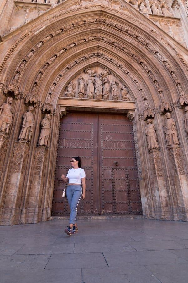Een jonge donkerbruine vrouw die voor de Kathedraal van Valencia Spain met wit overhemd en grijze broek lopen royalty-vrije stock fotografie