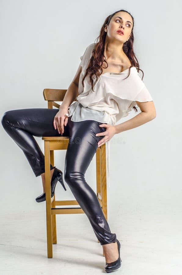 Een jonge donkerbruine vrouw in het witte overhemd stellen op een stoel agressief royalty-vrije stock afbeeldingen