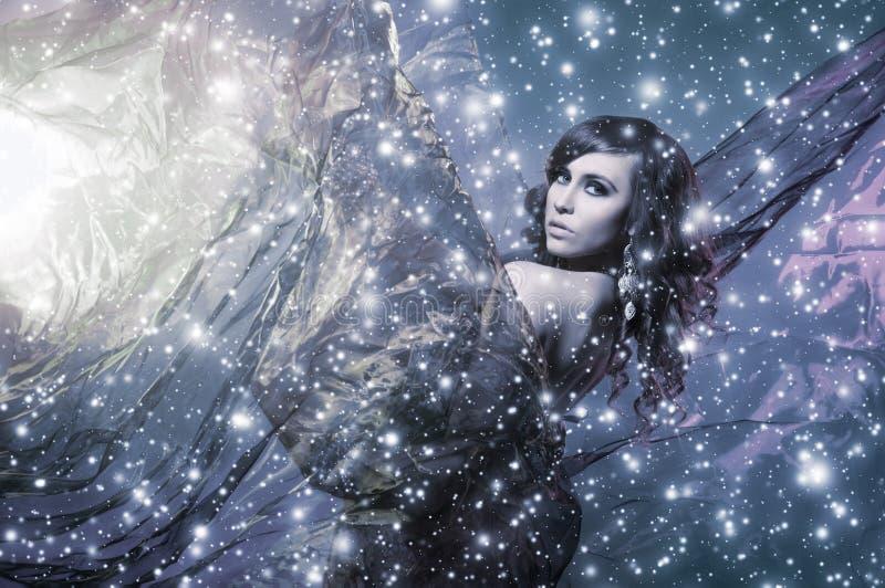 Een jonge donkerbruine vrouw op een sneeuwzijdeachtergrond stock foto