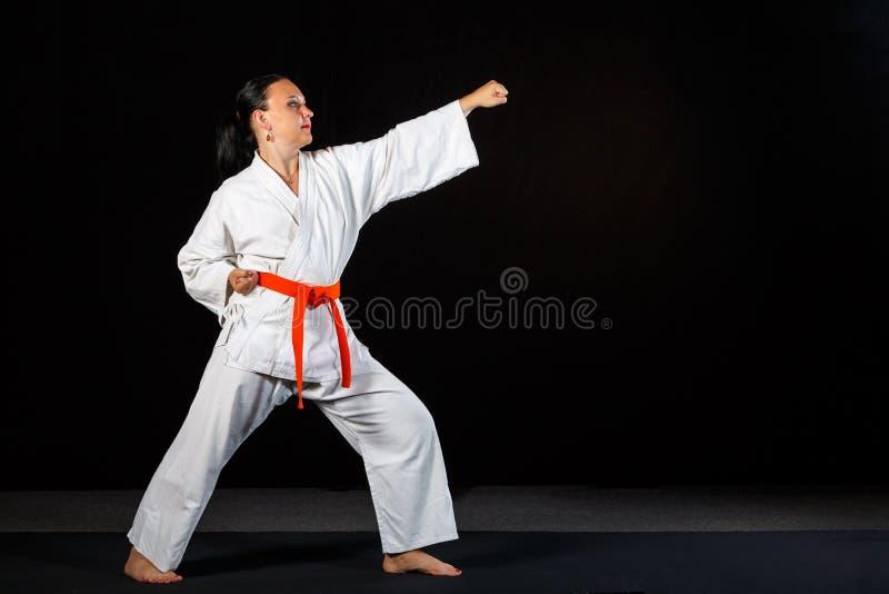 Een jonge donkerbruine vrouw in een witte kimono die karate op een zwarte achtergrond in de volledige groei doen stock afbeelding