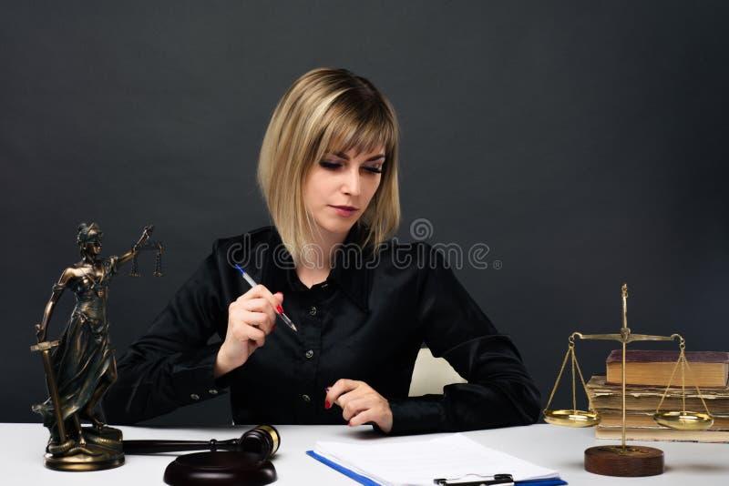 Een jonge eerlijke vrouwenrechter werkt in haar bureau royalty-vrije stock afbeeldingen