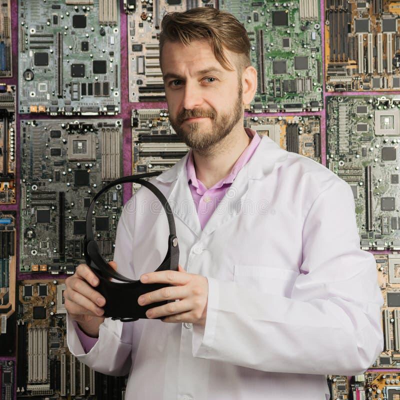 Een jonge elektronikaingenieur bevindt zich met een vergrootglas in zijn handen dichtbij de muur van motherboards stock fotografie