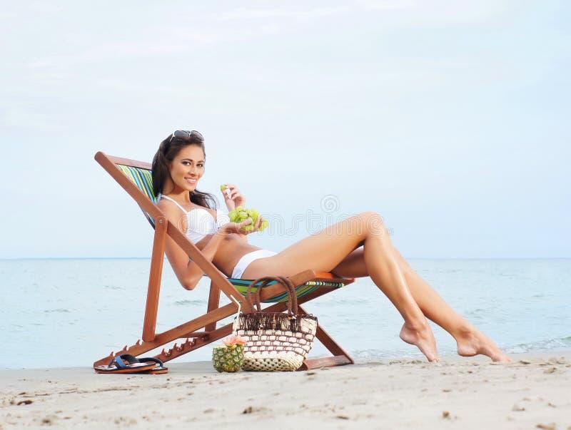 Een jonge donkerbruine vrouw die vruchten eten en op het strand ontspannen royalty-vrije stock afbeeldingen