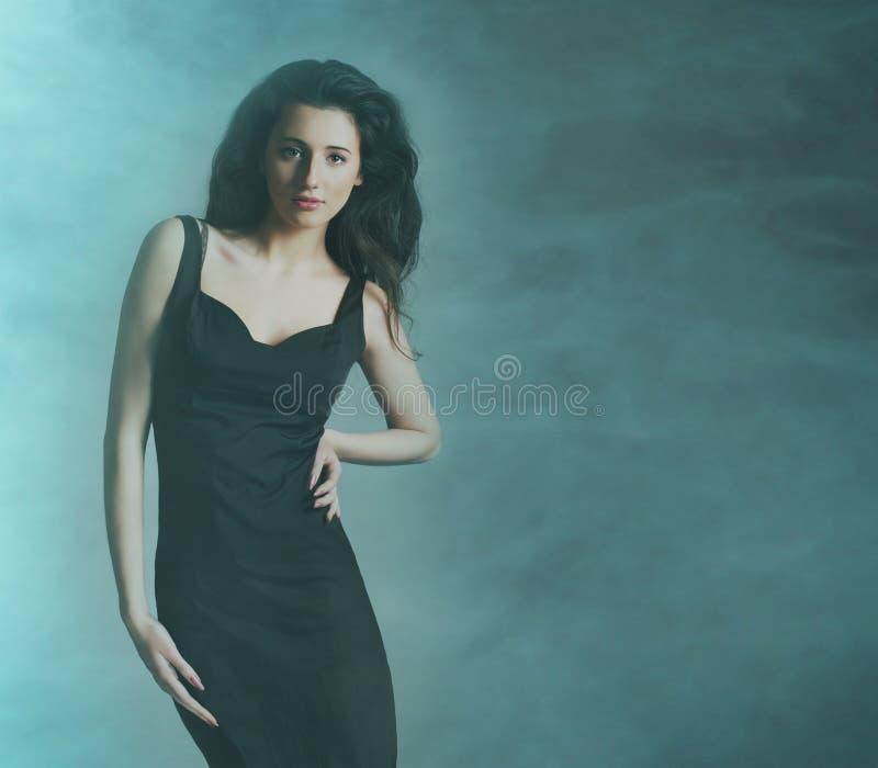 Een jonge en aantrekkelijke donkerbruine vrouw in de rook stock foto