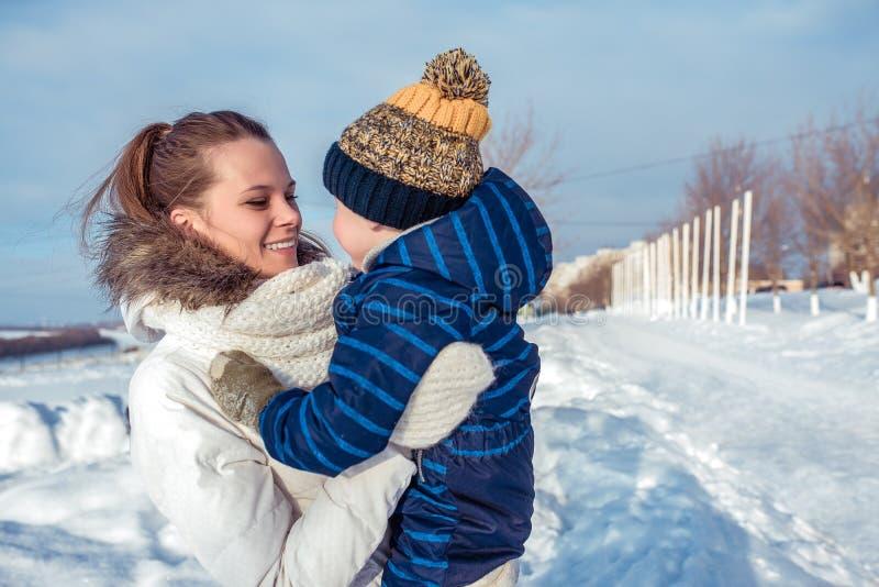 Een jonge en gelukkige moeder houdt het kind in haar wapens, glimlacht en verheugt zich De verse lucht van de straatwinter, een j royalty-vrije stock fotografie