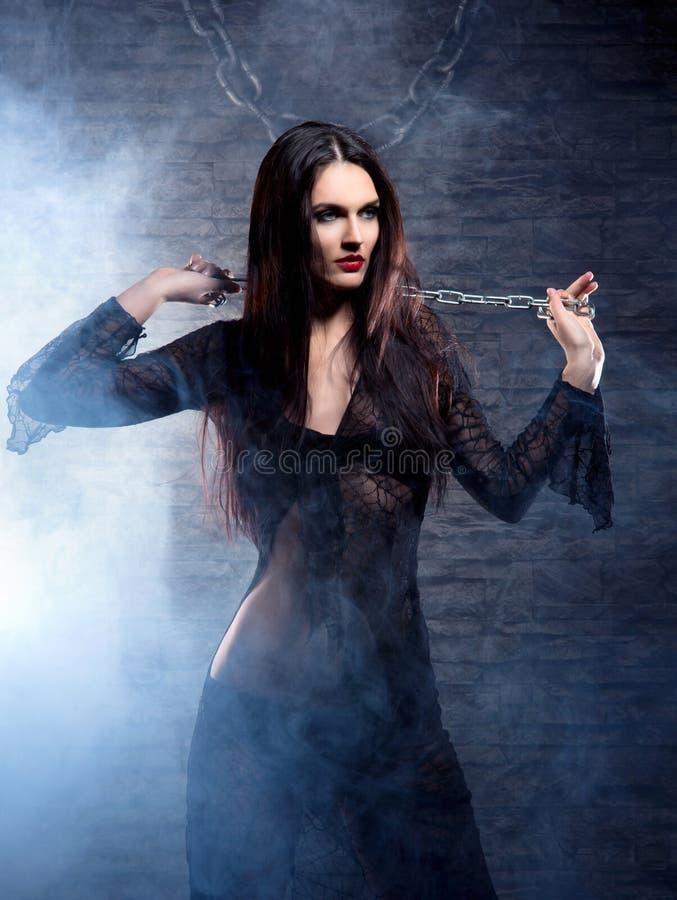 Een jonge en sexy heks in donkere erotische kleren stock afbeeldingen