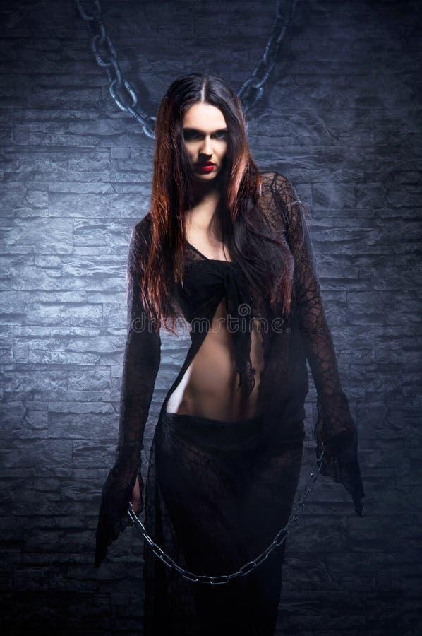 Een jonge en sexy heks in een lange zwarte kleding royalty-vrije stock foto's