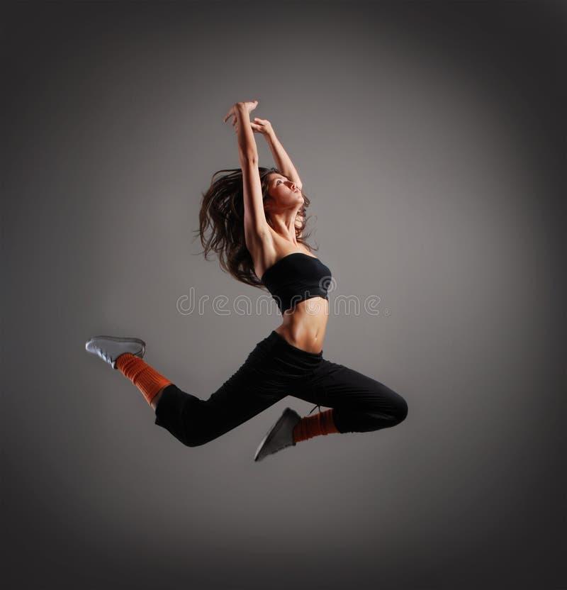 Een jonge en sportieve donkerbruine vrouw in een sprong royalty-vrije stock foto's