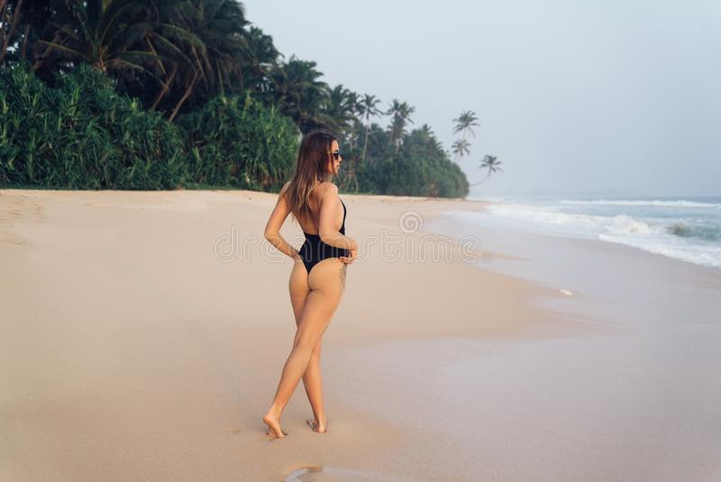 Een jonge Europese vrouw kwam enkel rusten, looppas langs een wit zandig strand, wil het blauwe zeewater raken Het concept royalty-vrije stock foto's