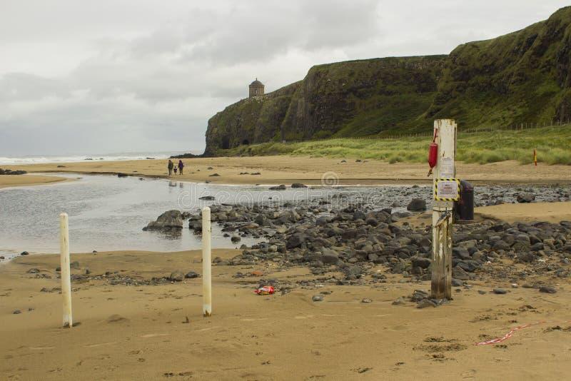 Een jonge familie die over bergaf strand in Provincie Londonderry in Noord-Ierland met Mussenden-Tempel wandelen stock afbeeldingen