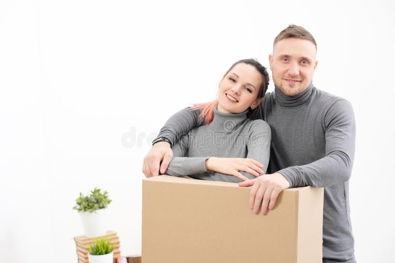 Een jonge familie, een man en een vrouw in grijze sweaters verplaatsen naar nieuwe flats Dozen met lading op een wit royalty-vrije stock foto