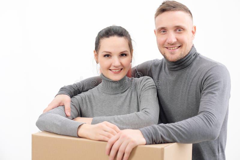 Een jonge familie, een man en een vrouw in grijze sweaters verplaatsen naar nieuwe flats Dozen met lading op een wit stock afbeelding