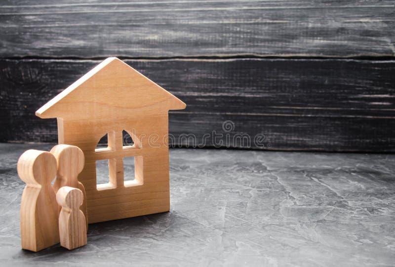 Een jonge familie met een kind bevindt zich dichtbij het huis Blokhuis en cijfers van mensen Het concept huisvestingsonderzoek, h royalty-vrije stock foto
