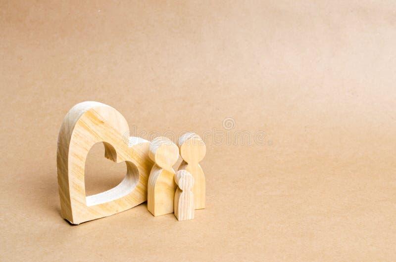 Een jonge familie met een kind bevindt zich dichtbij een houten hart Liefde en loyaliteit, een sterke jonge familie Familieverhou stock foto