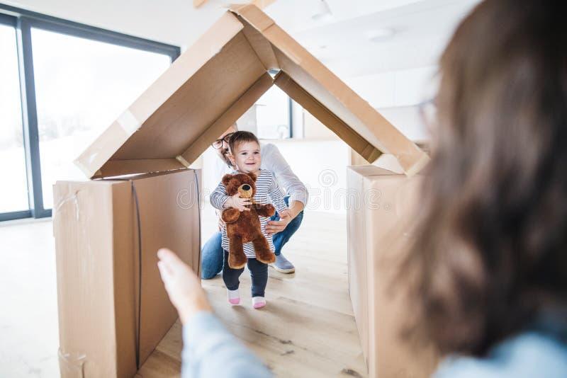Een jonge familie met een peutermeisje die binnen, zich in nieuw huisconcept bewegen stock fotografie
