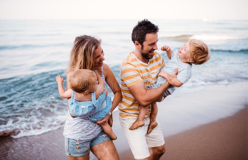 Een jonge familie met twee peuterkinderen die op strand op de zomervakantie lopen stock afbeelding