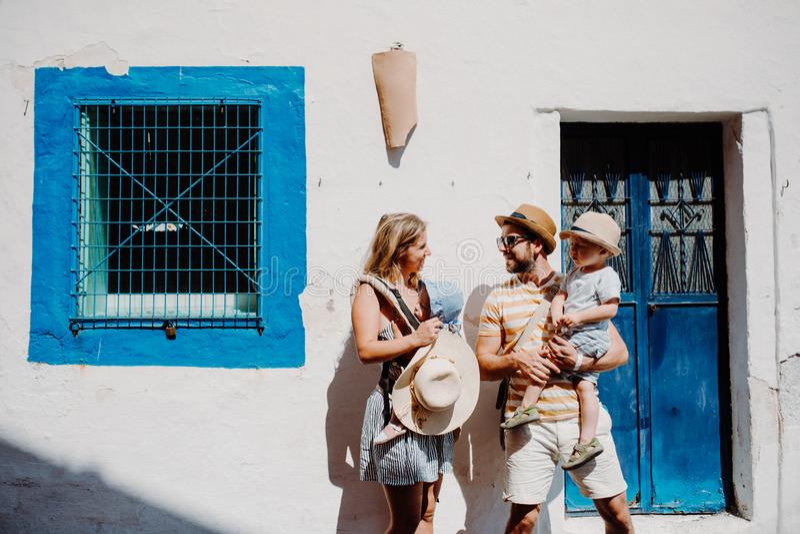 Een jonge familie met twee peuterkinderen die zich in stad op de zomervakantie bevinden stock foto