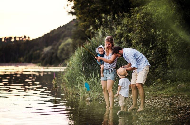 Een jonge familie met twee peuterkinderen in openlucht door de rivier in de zomer royalty-vrije stock afbeelding