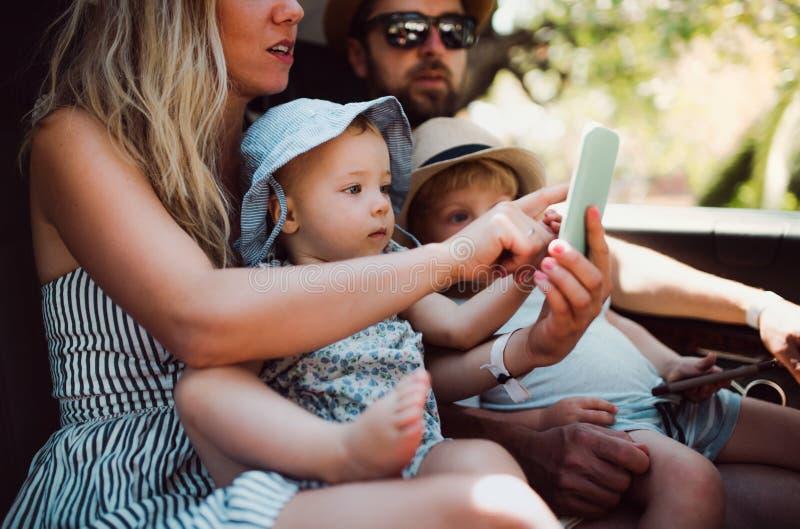 Een jonge familie met twee peuterkinderen in taxi op de zomervakantie stock foto's