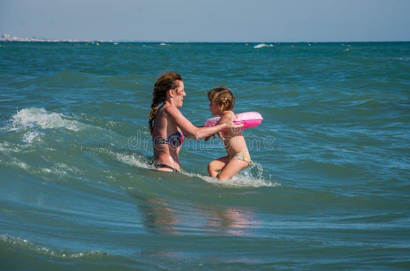 Een jonge familie, een moeder en een dochter met een zwemmende cirkel, die op het strand op het strand van de Thyrreense Zee spel stock foto