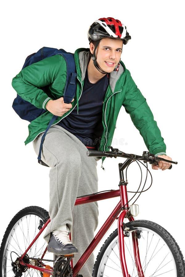 Een jonge fietser op fiets het stellen stock foto