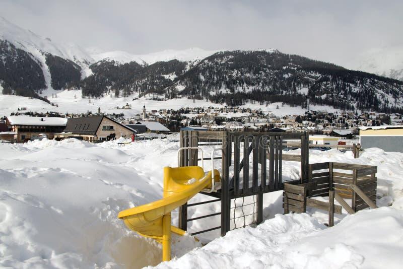 Een jonge geitjesspeelplaats onder sneeuw en sneeuwbergen en een kleine stad in de alpen Zwitserland stock afbeeldingen
