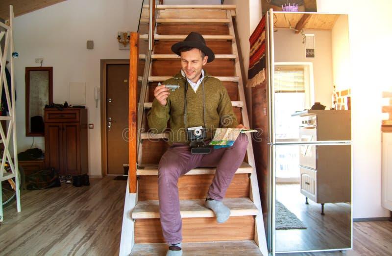 Een jonge gelukkige mens in een hoed houdt een vliegtuig en de kaart treft voor de reis in een flat voorbereidingen, hangt een ca stock foto's