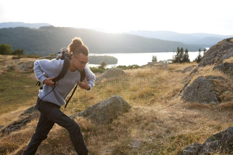 Een jonge gemengde rasmens die alleen in de bergen lopen stock fotografie